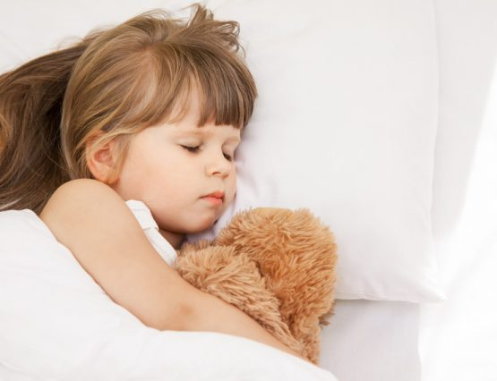 Girl sleeping in white bed at home. People, children, rest and comfort  concept
